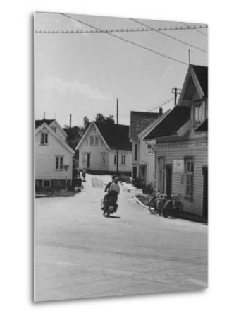 Motorcycle Going Down Street in Small Town--Metal Print