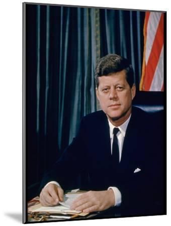 Pres. John F. Kennedy Sitting at His Desk, with Flag in Bkgrd-Alfred Eisenstaedt-Mounted Photographic Print