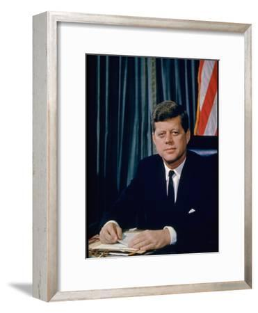Pres. John F. Kennedy Sitting at His Desk, with Flag in Bkgrd-Alfred Eisenstaedt-Framed Photographic Print