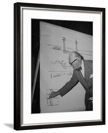 Swiss Architect Le Corbusier Standing on Stage with Notes in His Hand and Drawing on Sketch Pad--Framed Photographic Print
