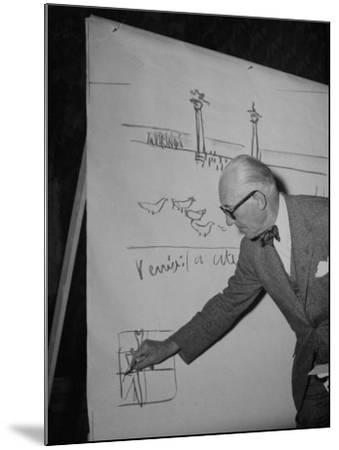 Swiss Architect Le Corbusier Standing on Stage with Notes in His Hand and Drawing on Sketch Pad--Mounted Photographic Print