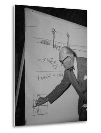 Swiss Architect Le Corbusier Standing on Stage with Notes in His Hand and Drawing on Sketch Pad--Metal Print