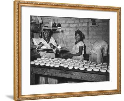 Women Stacking Loaves of Bread on Wooden Table, in Primitive Village of Zoogocho--Framed Photographic Print