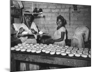 Women Stacking Loaves of Bread on Wooden Table, in Primitive Village of Zoogocho--Mounted Photographic Print
