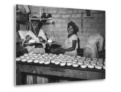Women Stacking Loaves of Bread on Wooden Table, in Primitive Village of Zoogocho--Metal Print