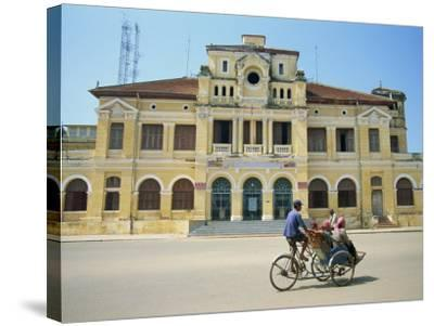 Cyclo Passing the Old Post Office in Phnom Penh in Cambodia, Indochina, Southeast Asia-Tim Hall-Stretched Canvas Print