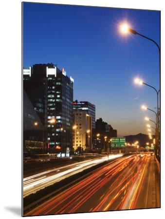 Car Light Trails and Modern Architecture on a City Ring Road, Beijing, China-Kober Christian-Mounted Photographic Print