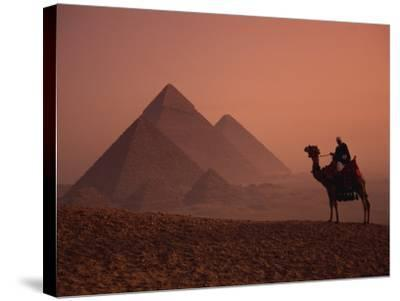 Camel and Rider at Giza Pyramids, UNESCO World Heritage Site, Giza, Cairo, Egypt-Howell Michael-Stretched Canvas Print