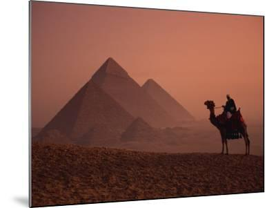 Camel and Rider at Giza Pyramids, UNESCO World Heritage Site, Giza, Cairo, Egypt-Howell Michael-Mounted Photographic Print