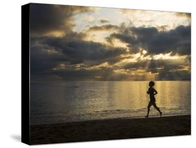 Silhouetted Woman Jogging on a Beach at Twilight-Mattias Klum-Stretched Canvas Print