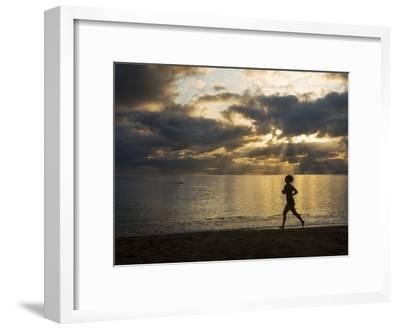 Silhouetted Woman Jogging on a Beach at Twilight-Mattias Klum-Framed Photographic Print
