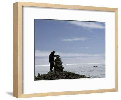 Inuit Hunter Surveys a Sacred Inuksuk Monument, Used as a Waypost-Gordon Wiltsie-Framed Photographic Print
