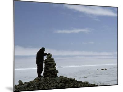 Inuit Hunter Surveys a Sacred Inuksuk Monument, Used as a Waypost-Gordon Wiltsie-Mounted Photographic Print