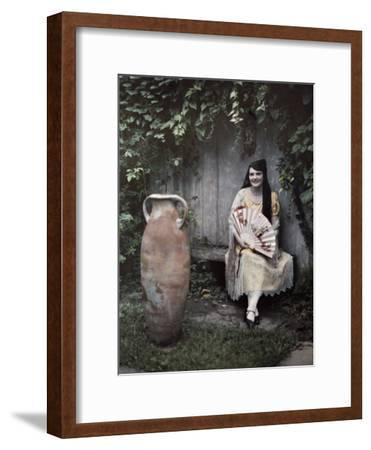 Young Lady Sits on a Bench by a Vase in a French Quarter Garden-Edwin L^ Wisherd-Framed Photographic Print