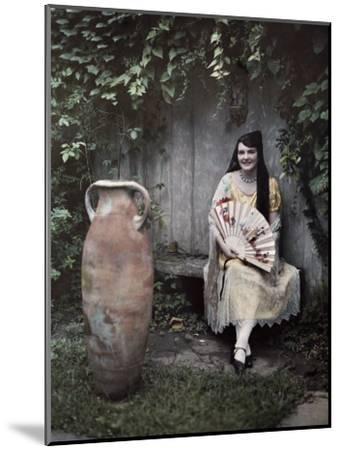 Young Lady Sits on a Bench by a Vase in a French Quarter Garden-Edwin L^ Wisherd-Mounted Photographic Print