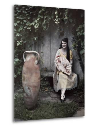 Young Lady Sits on a Bench by a Vase in a French Quarter Garden-Edwin L^ Wisherd-Metal Print