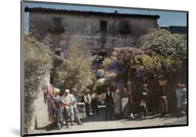 Locals Gather under Flowered Gateways Outside Rome-Hans Hildenbrand-Mounted Photographic Print