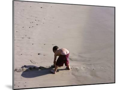 Boy's Bottom Peeks Out from His Bathing Suit as He Plays in Sand-White & Petteway-Mounted Photographic Print