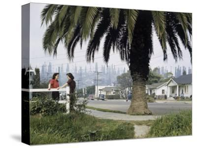 Two Girls Chat on a Street with Oil Derricks in the Background-B^ Anthony Stewart-Stretched Canvas Print