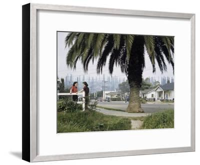 Two Girls Chat on a Street with Oil Derricks in the Background-B^ Anthony Stewart-Framed Photographic Print