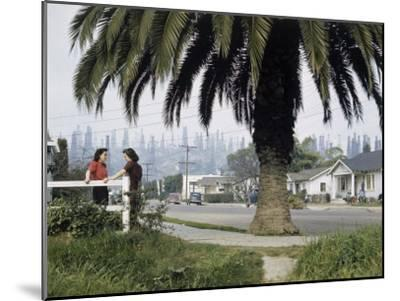 Two Girls Chat on a Street with Oil Derricks in the Background-B^ Anthony Stewart-Mounted Photographic Print