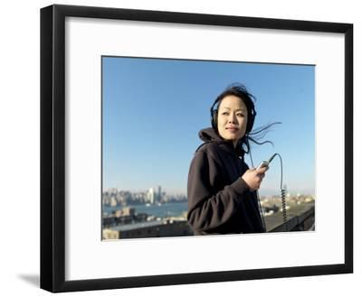 Young Asian Woman Listens to Her Headphones While Looking Away-xPacifica-Framed Photographic Print