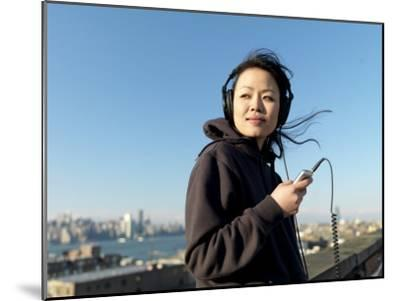 Young Asian Woman Listens to Her Headphones While Looking Away-xPacifica-Mounted Photographic Print