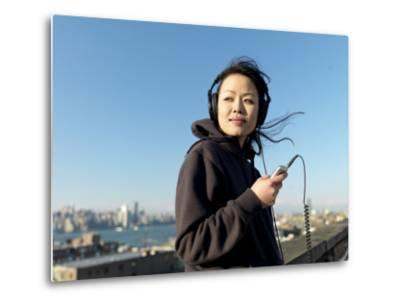 Young Asian Woman Listens to Her Headphones While Looking Away-xPacifica-Metal Print