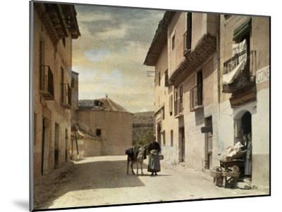 Woman and Donkey Stand in an Empty Street in Segovia-Gervais Courtellemont-Mounted Photographic Print