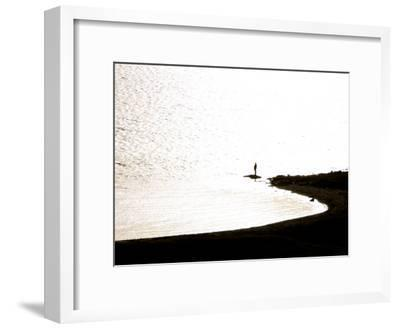 Silhouetted Person on a Point of Land Jutting Out into Calm Water-Mattias Klum-Framed Photographic Print