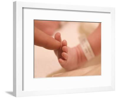 Father Touching His Newborn Sons' Foot-Greg Dale-Framed Photographic Print