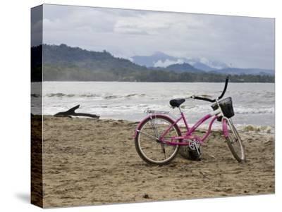 Pink Bike Sits on the Beach in Cahuita National Park-Hannele Lahti-Stretched Canvas Print