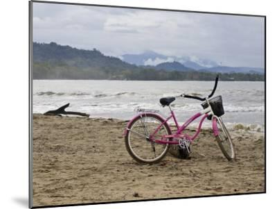 Pink Bike Sits on the Beach in Cahuita National Park-Hannele Lahti-Mounted Photographic Print