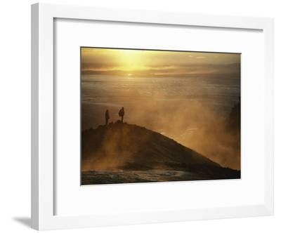 Two Silhouetted Men at Twilight Amid Geothermal Steam on Mountain Top-Paul Chesley-Framed Photographic Print