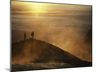 Two Silhouetted Men at Twilight Amid Geothermal Steam on Mountain Top-Paul Chesley-Mounted Photographic Print