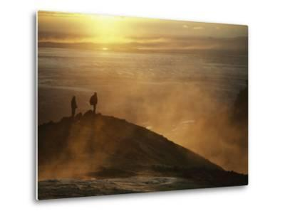 Two Silhouetted Men at Twilight Amid Geothermal Steam on Mountain Top-Paul Chesley-Metal Print
