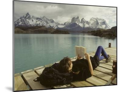 Woman Relaxes on a Dock While Reading a Book-Skip Brown-Mounted Photographic Print