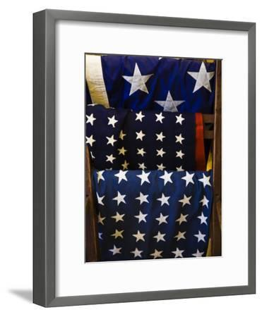 Us Flags Folded and Hanging from a Wooden Rack-Todd Gipstein-Framed Photographic Print