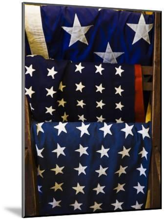 Us Flags Folded and Hanging from a Wooden Rack-Todd Gipstein-Mounted Photographic Print