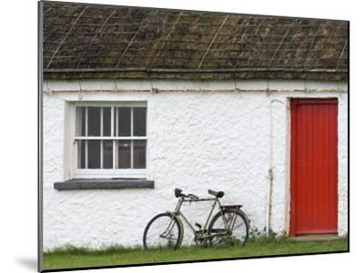 Historic Thatched Roof House with a Red Door and Old Bicycle-Rich Reid-Mounted Photographic Print