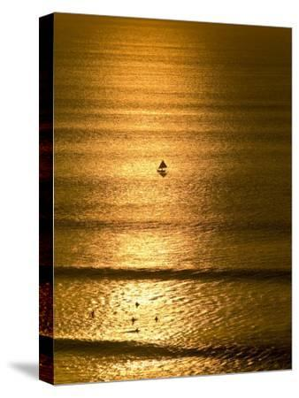 Small Fishing Boat Heads Out to Sea at Sunset Past Surfers-Jason Edwards-Stretched Canvas Print