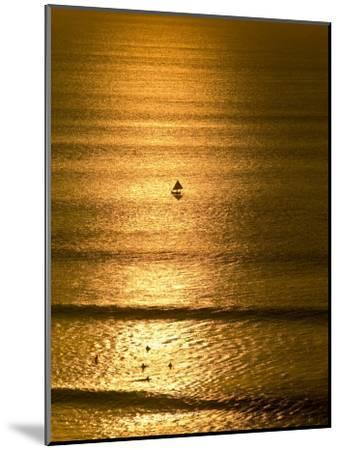 Small Fishing Boat Heads Out to Sea at Sunset Past Surfers-Jason Edwards-Mounted Photographic Print
