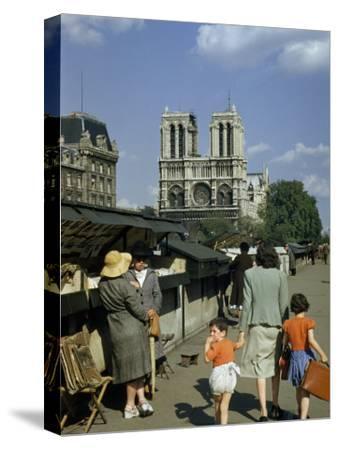Mother Hurries Children Past Book Stalls Near Notre Dame De Paris-Justin Locke-Stretched Canvas Print