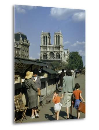 Mother Hurries Children Past Book Stalls Near Notre Dame De Paris-Justin Locke-Metal Print