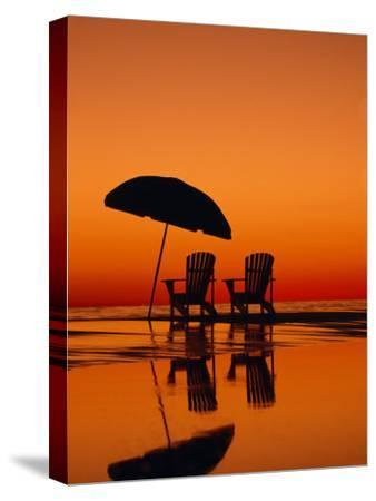 Picturesque Scene with Two Chairs and an Umbrella on the Beach-Michael Melford-Stretched Canvas Print