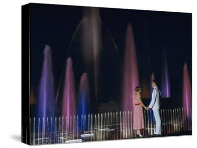 Couple Holding Hands Watches Water Fountains Illuminated at Night-B^ Anthony Stewart-Stretched Canvas Print