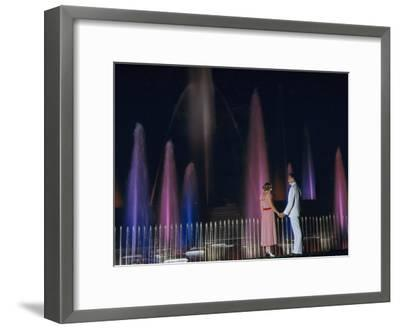 Couple Holding Hands Watches Water Fountains Illuminated at Night-B^ Anthony Stewart-Framed Photographic Print