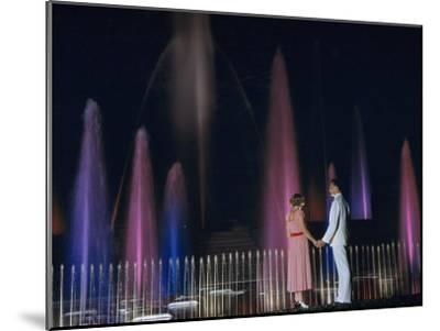Couple Holding Hands Watches Water Fountains Illuminated at Night-B^ Anthony Stewart-Mounted Photographic Print