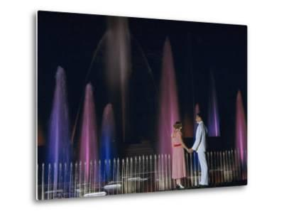 Couple Holding Hands Watches Water Fountains Illuminated at Night-B^ Anthony Stewart-Metal Print