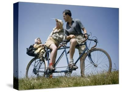 Man and Woman Straddling Tandem Bicycle Look at Child in Back Seat-B^ Anthony Stewart-Stretched Canvas Print